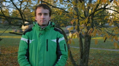 Young handsome man looking into the camera in autumn park. Equip a green sports Stock Footage