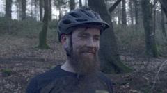 Portrait of a man mountain biking in the woods wearing a helmet, super slow moti Stock Footage