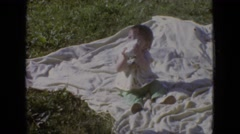 1965: a baby sits on a blanket in the grass, drinking from a paper cup  Stock Footage