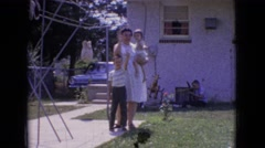 1965: a woman outside with a boy waving as she holds a baby in one arm  Stock Footage