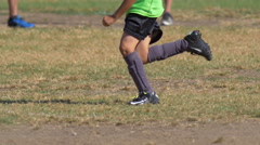 Details of a ball and boys legs playing youth soccer football on a grass field. Stock Footage