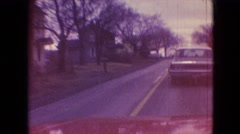 1966: a white car is being chased by a red car along the avenue ATHENS OHIO Stock Footage