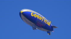 The Goodyear Tires blimp flying in the blue sky. Stock Footage