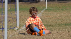 A goalie playing youth soccer football on a grass field, slow motion. Stock Footage