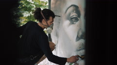 4K Masked graffiti artist creating portrait of a woman's face on city wall Stock Footage