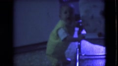 1966: a baby dressed in yellow using a chair to stand ATHENS OHIO Stock Footage