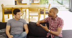 4K Young male friends relaxing at home & having serious conversation Stock Footage