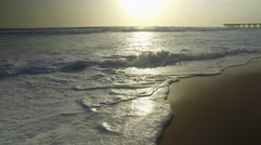 Tracking shot of the ocean waves, beach and pier at sunset. Stock Footage
