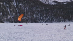A snowkiter trying to lift his kite on a frozen lake in the Switzerland Alps Stock Footage