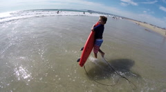A boy carries his surfboard to the waves at the beach. Stock Footage