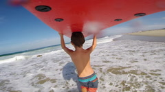 POV of a boy carrying his surfboard at the beach, slow motion. Stock Footage