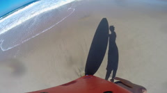 POV and shadow of a boy with his surfboard at the beach, slow motion. Stock Footage