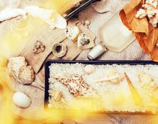 A lot of sea theme in mess like shells, candles, perfume, girl stuff on linen Stock Photos