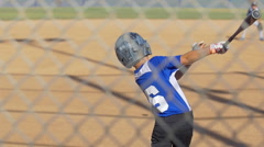 A batter makes a base hit while playing in a boys little league baseball game, s Stock Footage