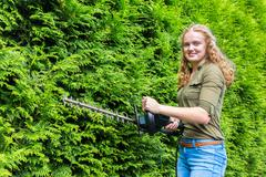 Young dutch woman holding hedge trimmer at conifers Stock Photos