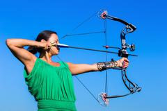 Young woman aiming arrow of compound bow Stock Photos