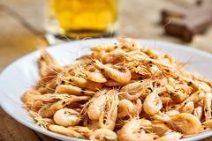 Boiled shrimp on white plate, beer mug behind Stock Photos