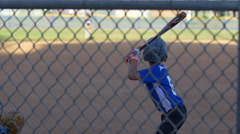 A batter makes a strike while playing in a boys little league baseball game, slo Stock Footage