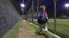 A boy walking with his bat bag after a little league baseball game. Stock Footage