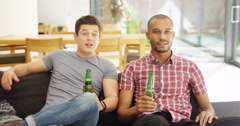 4k, Young male friends watching a match on tv. One celebrates while other sulks  Stock Footage