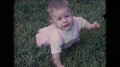 1966: cute baby crawling grass looking back talking enjoying ATHENS OHIO Stock Footage