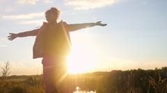 Mature woman standing on the rock rises her hands jumps through the sun joyful Stock Footage