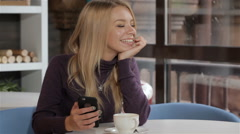 Woman messages by her cellphone at the cafe Stock Footage