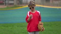 A boy eats sunflower seeds on a little league baseball field, super slow motion. Stock Footage