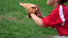A boy practices playing catch on a little league baseball field, super slow moti Stock Footage