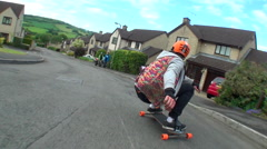 A young man longboard skateboarding downhill in a residential neighborhood. Stock Footage