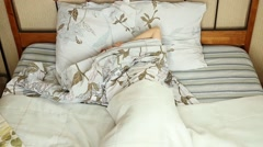 Young blonde woman waking up stretching arms on the bed in the morning Stock Footage