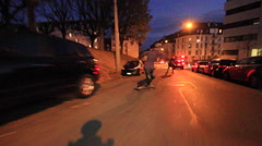 A group of young men longboard skateboarding downhill in a city at night. Stock Footage