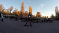 A group of friends longboard skateboarding downhill in a city park. Stock Footage