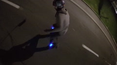 A young man longboard skateboarding downhill in a city at night with blue light Stock Footage