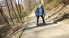 A young man longboard skateboarding downhill in a city park. Stock Footage
