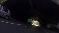 A young man longboard skateboarding downhill in a city through a tunnel, slow mo Stock Footage