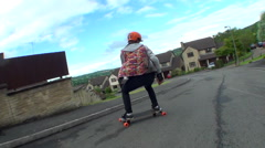 A young man longboard skateboarding downhill in a residential neighborhood, time Stock Footage