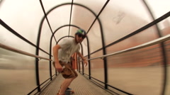 A young man longboard skateboarding downhill in a city through a tunnel, time-la Stock Footage