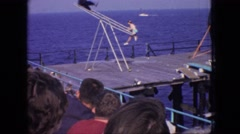 1966: acrobat show on dock of two people on a seesaw like structure, and a woman Stock Footage