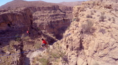 Aerial view of a man balancing while tightrope walking and slacklining across a Stock Footage