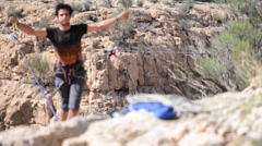 A man balances while tightrope walking and slacklining across a canyon. Stock Footage