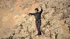 A man balances while tightrope walking and slacklining across a canyon, time-lap Stock Footage
