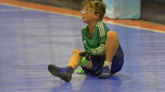 A boy is injured while playing futsal youth soccer football. Stock Footage