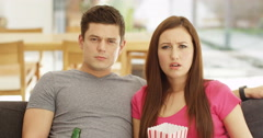 4K Couple watching TV at home, girl gets upset by something she sees on screen Stock Footage