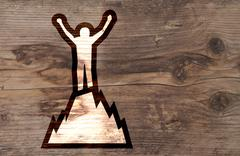 Illustration of man on top of mountain on brown wooden background Piirros