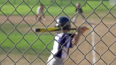 Boys play in a little league baseball game through a chain-link fence, super slo Stock Footage