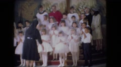 1966: a nun preparing candidates in white dresses for communion in a church  Stock Footage
