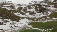 A trail runner runs up a snowy mountain. Stock Footage