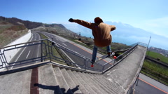 A young man does a trick on a skateboard down stairs. Stock Footage