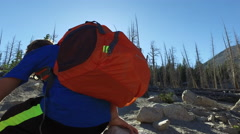 A boy hiking on a trail and sitting to take a break in the mountains. Stock Footage